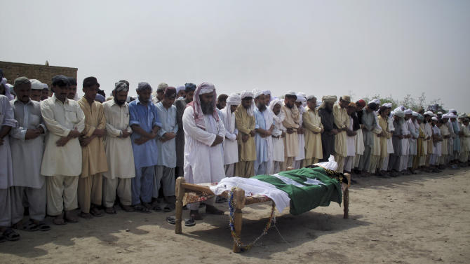 People offer funeral prayers for a police officer killed in the gun-battle with Taliban militants during an attack on a police station, Sunday, June 26, 2011 in Kolachi near Dera Ismail Khan, Pakistan. The Pakistani Taliban say they used a female suicide bomber for the first time in an attack on the police station in northwestern Pakistan. (AP Photo/Kashif Naveed)