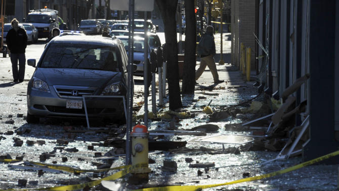 People walk in a damaged area about a block away from the site of a Friday-evening gas explosion that leveled a strip club in Springfield, Mass., Saturday, Nov. 24, 2012. Investigators are trying to figure out what caused the blast where the multistory brick building housing Scores Gentleman's Club once stood. (AP Photo/Jessica Hill)