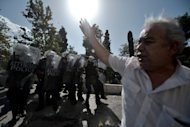 <p>A man gestures as riot police clashes with demonstrators during a 24-hour strike in Athens on October 18, 2012. About 25,000 protesters joined the rallies in Athens, called by unions and left-wing parties against the tough fiscal medicine that has spelled misery for many Greeks.</p>
