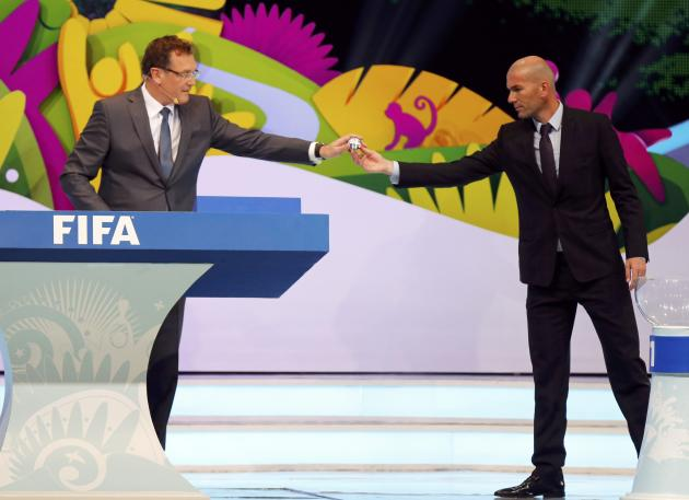 Former France soccer player Zinedine Zidane hands a ball that he had drawn from a pot to FIFA Secretary General Jerome Valcke during the draw for the 2014 World Cup at the Costa do Sauipe resort in Sa