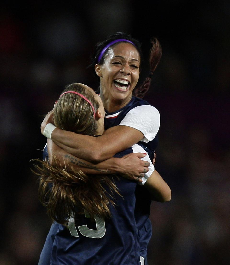 United States' Sydney Leroux, top, celebrates with scorer of the winning goal Alex Morgan following their semifinal win over Canada in a women's soccer match at the 2012 London Summer Olympics, Monday, Aug. 6, 2012 at Old Trafford Stadium in Manchester, England. (AP Photo/Jon Super)