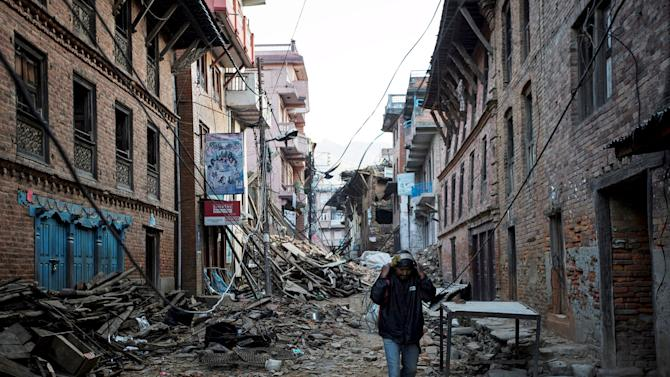 An earthquake victim carries belongings along a street near the collapsed houses in Sankhu, on the outskirts of Kathmandu