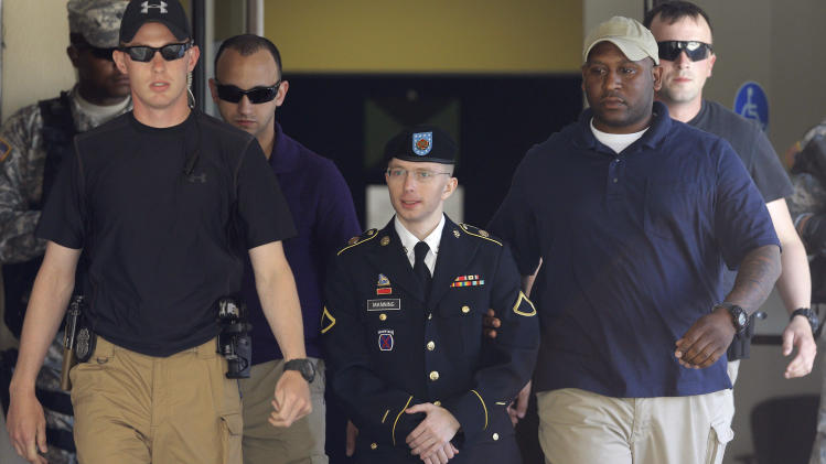 FILE -In this Tuesday, June 4, 2013 file photo, Army Pfc. Bradley Manning, center, is escorted out of a courthouse in Fort Meade, Md., after the second day of his court martial. Visual journalists from many organizations have experienced difficulty capturing an unobstructed view of Manning entering and exiting a courthouse on the U.S. Army Post Fort Meade because of the often heavy security presence around him. (AP Photo/Patrick Semansky, File)