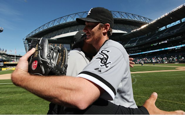 Chicago White Sox starting pitcher Phil Humber, right, is hugged after pitching a perfect baseball game against the Seattle Mariners, Saturday, April 21, 2012, in Seattle. The White Sox won 4-0. (AP P
