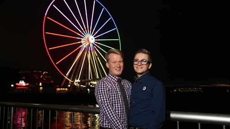 Zac Baker and Sam Busch from St. Paul, MN await a VIP ride on Seattle's Great Wheel, Tuesday, September 2, 2014, the night before they wed in the Emerald City. This waterfront icon, along with numerous other Seattle landmarks show their true colors with rainbow lights and flags to demonstrate the city's embrace of marriage equality. Sam and Zac will wed in a ceremony tomorow officiated by Seattle's first openly gay mayor, Ed Murray. The ceremony is the first of four Marry Me in Seattle weddings hosted by the city's tourism community in an effort to increase LGBTQ visits to Seattle. Ron Wurzer/AP Images for Visit Seattle