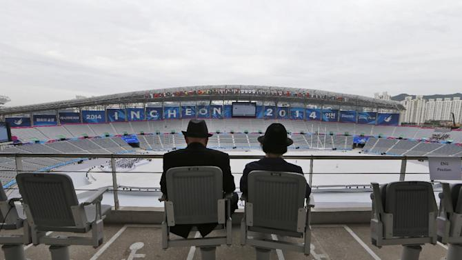A couple sits at the Incheon Asiad Main Stadium where the opening ceremony of the 17th Asian Games will be held in Incheon, South Korea Wednesday, Sept. 17, 2014. The games will be held in the South Korea's western city from Sept. 19 to Oct. 4. (AP Photo/Kin Cheung)
