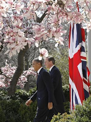 President Barack Obama and British Prime Minister David Cameron walk to their joint news conference in the Rose Garden of the White House in Washington, Wednesday, March 14, 2012. (AP Photo/Charles Dharapak)