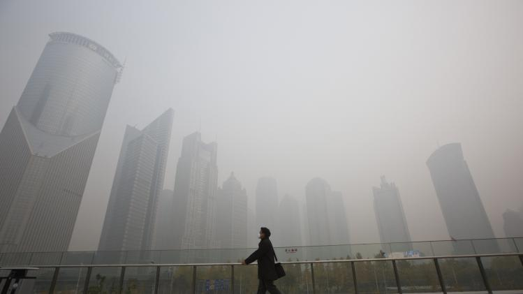 A man wearing a face mask walks on a pedestrian overpass on a hazy day at the Pudong financial area in Shanghai