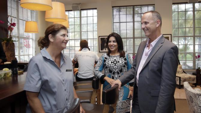 In this photo taken Wednesday, July 17, 2013, Yolanda Oruc, left, talks to general manager Jeff Lehman, right, and HR director Nilmarie Almdovar, center, in the lobby of the Betsy Hotel in the South Beach area of Miami Beach, Fla. Uruguayan native Yolanda Oruc said she could have become an American citizen three years ago but didn't have the money to pay for attorney's fees. So when the 52-year-old mini bar attendant learned that her employer had brought in immigration experts to help her fill out the papers, she jumped at the chance and naturalized earlier this month. (AP Photo/Alan Diaz)