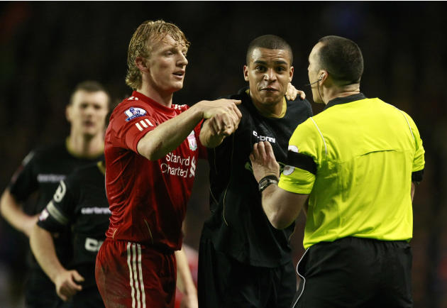 Oldham Athletic's Tom Adeyemi, second right, is calmed by Liverpool's Dirk Kuyt and referee Neil Swarbrick, right, during their FA Cup third round soccer match at Anfield, Liverpool, England, Friday J
