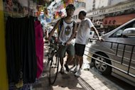A cyclist makes his way along a footpath in Hong Kong. Potential cyclists, who may be put off by the lack of bicycle parking, will also be tempted by Hong Kong&#39;s ultra-efficient transport system, which includes metros, buses and trams