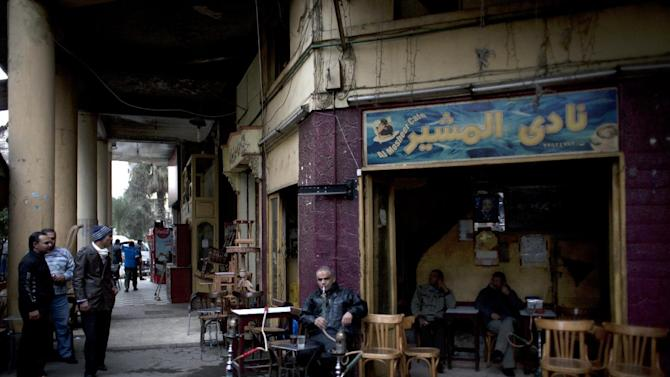 "In this Tuesday, Jan. 8, 2013 photo, an Egyptian man smokes a water pipe at 'al-Mosheer cafe,' a traditional coffee shop that was established more than forty years ago on Mohammed Ali street, a street that is home to musicians, belly-dancers and instrument makers, in downtown Cairo, Egypt. The street, named after the founder of modern Egypt, was built in the 1860s as part of a new downtown that was to modernize Cairo. Inspired by French architect Baron Haussmann, the designer of Paris' grand boulevards, Egypt's then-ruler Khedive Ismail sought to ""make Egypt a piece of Europe."" The result was a downtown of avenues and city squares lined with arches and European architecture, between the Nile and the old medieval city of Cairo, with its Islamic architecture and maze of narrow alleys. (AP Photo/Nasser Nasser)"
