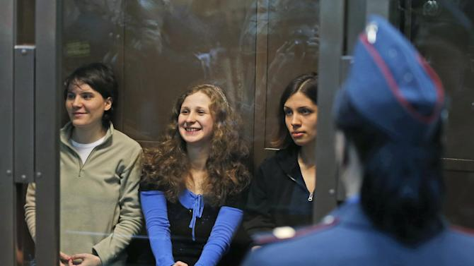 FILE - In this Oct. 10, 2012 file photo. feminist punk group Pussy Riot members, from left, Yekaterina Samutsevich, Maria Alekhina, and Nadezhda Tolokonnikova sit in a glass cage at a court room in Moscow. Russia's Prime Minister Dmitry Medvedev said Friday, Nov. 2, 2012 that he detested the Pussy Riot act, but added the women have been in prison long enough and should be released. (AP Photo/Sergey Ponomarev, File)