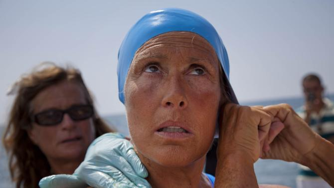 FILE - This Aug. 18, 2012 file photo shows Diana Nyad adjusting her swimming cap as a woman applies a protective ointment to her skin as she prepares to jump into the water and start her swim to Florida from Havana, Cuba. Her goal of swimming from Cuba to Florida appearing elusive, Nyad was out of the water Tuesday morning, Aug. 21, 2012, being checked by doctors on a boat and discussing whether she could return to a fourth day of swimming. (AP Photo/Ramon Espinosa, File)