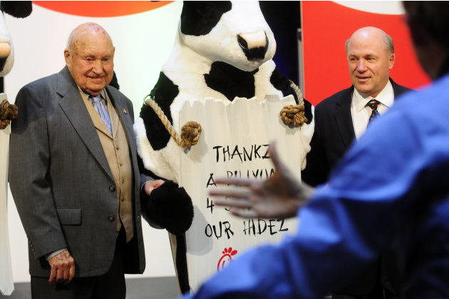 FILE - In this Monday, Dec. 14, 2009 file picture, Chick-fil-a founder Truett Cathy, left, and his son Dan Cathy pose for a photo with the Chick-fil-A cows during a celebration of passing the $3 billo