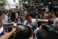 Opposition Pheu Thai Party leader Yingluck Shinawatra, left, is surrounded by reporters after casting her ballot at a voting station in Thailand's general election on Sunday, July 3, 2011 in Bangkok, Thailand.(AP Photo/Vincent Yu)