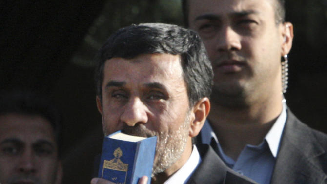 Iranian President Mahmoud Ahmadinejad, center, kisses the Quran Monday, Sept. 19, 2011, as he leaves Tehran's Mehrabad airport, Iran, bound for New York, U.S.A.  to attend the UN General Assembly.   (AP Photo/Vahid Salemi)