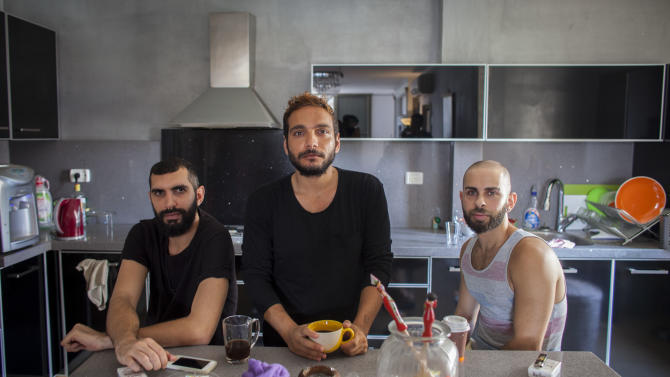 """This Monday, July 27, 2015 photo, shows Fadi Daeem, from left, Khader Abu Seif and Naeem Jiryes, protagonists of the documentary movie """"Oriented"""" during an interview with The Associated Press in Jaffa, mixed Jewish-Arab part of Tel Aviv, Israel. The movie follows the lives of the three gay Palestinian friends in Tel Aviv, confronting their national and sexual identity. (AP Photo/Eyal Warshavsky)"""