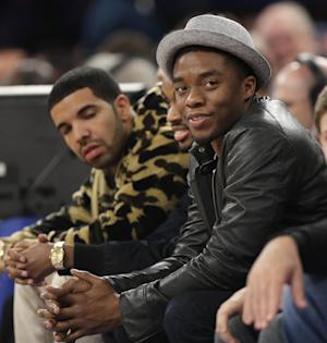 """FILE - Actor Chadwick Boseman, right, is seen Sunday, April 14, 2013 during the second half of the NBA basketball game between the Indiana Pacers and the New York Knicks in New York. Boseman has been cast to play James Brown., the Godfather of Soul, in a planned biopic by """"The Help"""" director Tate Taylor. The film from Universal Pictures and Imagine Entertainment is currently untitled. Mick Jagger and Brian Grazer are among the producers. (AP Photo/Seth Wenig, File)"""
