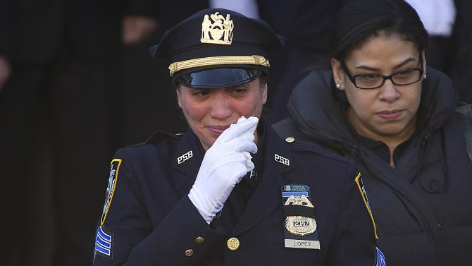 A police officer cries as she departs the funeral of slain NYPD officer Rafael Ramos at Christ Tabernacle Church to it's final resting place in the Queens borough of New York