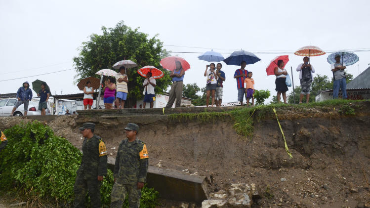 Mexican army soldiers on duty for emergency relief stand next to villagers as they watch workers reinforce a road with sandbags, not seen, in Acapulco, Mexico, Monday, Oct. 21, 2013. The area is on alert as Hurricane Raymond gained more strength and threatened to hurl heavy rains onto a sodden region already devastated by last month's Tropical Storm Manuel. (AP Photo/Bernandino Hernandez)