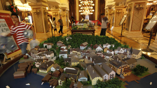 A worker walks past a diorama of an European-style houses in Hallstatt See, a replica of the Austrian town of Hallstatt, in Boluo county, Huizhou city, south China's Guangdong province Saturday, June 2, 2012. A group of Austrians whose scenic mountain village has been copied down to the statues by a Chinese developer attended Saturday's opening in China for the high-end residential project but were still miffed about how the company did it. The original is a centuries-old village of 900 people and a UNESCO heritage site that survives on tourism. The copycat is a housing estate that thrives on China's new rich. In a China famous for pirated products, the replica Hallstatt sets a new standard. (AP Photo/Vincent Yu)
