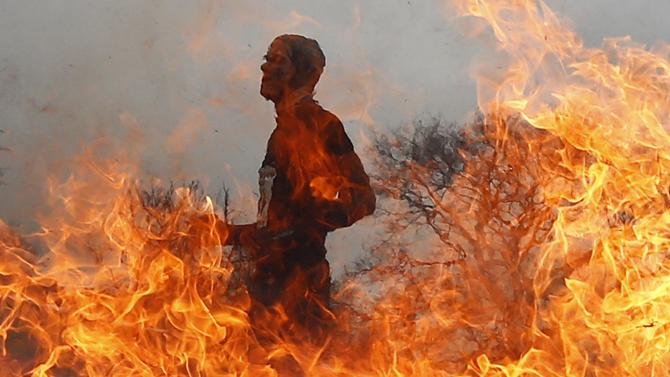 Competitor runs through a burning obstacle during the Tough Guy event in Perton