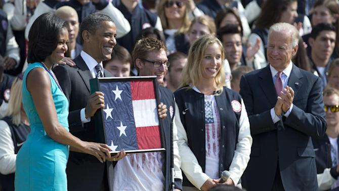 From left, first lady Michelle Obama, President Barack Obama, U.S. Paralympic flag bearer and Navy Veteran Brad Snyder, U.S. Olympic flag bearer Mariel Zagunis, and Vice President Joe Biden, take part in a ceremony on the South Lawn of the White House in Washington, Friday, Sept. 14, 2012,  to welcome the 2012 U.S. Olympic and Paralympic teams. President Obama was presented with the flag carried by Zagunis and Snyder during the Olympics. (AP Photo/Carolyn Kaster)