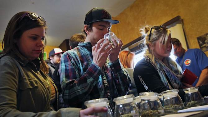 Customers, left to right, Alli Bertucci, Patrick Bean, and Ali Regan shop for marijuana inside the retail store at 3D Cannabis Center, in Denver, Friday Feb. 14, 2014. The marijuana industry breathed a sigh of relief Friday after federal banking regulators issued long-awaited permission for them to access basic banking services. (AP Photo/Brennan Linsley)