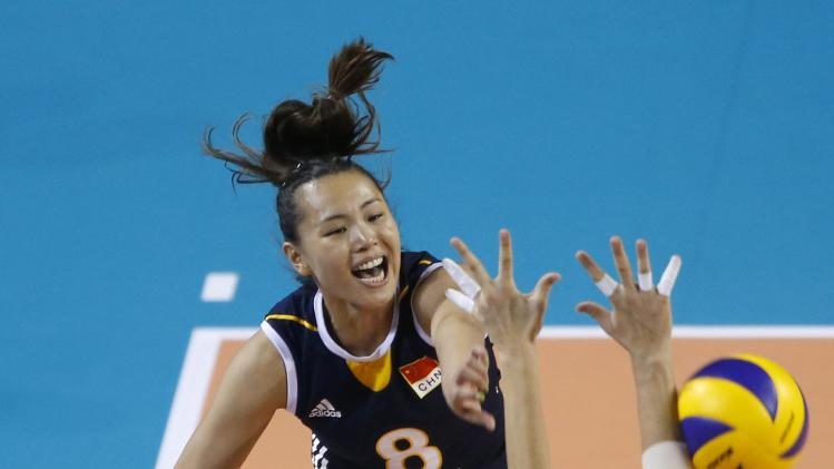 Zeng of China spikes the ball against Ozsoy of Turkey during their FIVB Women's Volleyball World Grand Prix 2014 final round match in Tokyo