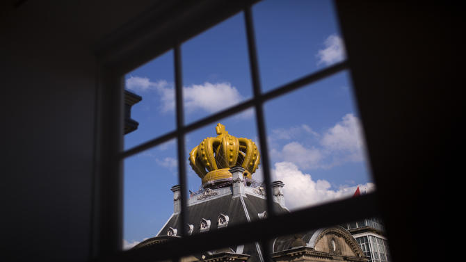 A large inflatable crown sits on top of a building in downtown Amsterdam, Netherlands Sunday, April 28, 2013. Queen Beatrix announced she will relinquish the crown on April 30, 2013, after 33 years of reign, leaving the monarchy to her son Crown Prince Willem Alexander.  (AP Photo/Emilio Morenatti)