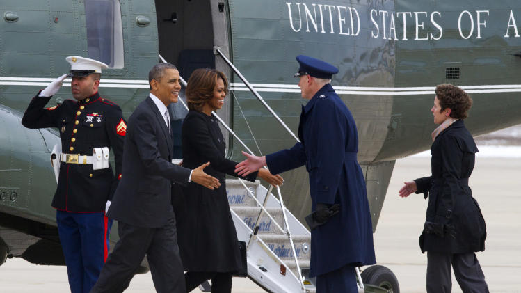 A Marine salutes as President Barack Obama and first lady Michelle Obama are greeted by 89th Airlift Wing Commander Col. David Almand and his wife Cathy Almand at Andrews Air Force Base, Md., Friday, March 7, 2014, before boarding Air Force One for a trip to Florida. (AP Photo/Jacquelyn Martin)