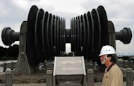 A Taiwan Power Co. (Taipower) employee walks past a low-pressure turbine rotor on display in Wanli earlier this year. The head of Taipower -- Taiwan&#39;s state electricity supplier -- has resigned after a steep hike in utility rates prompted outrage
