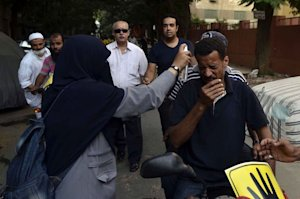A woman sprays water on a fellow protester to ease …