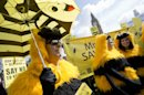 Bee-keepers and apiarists dressed up as bees demonstrate outside the Palace of Westminster as they ramp up their campaign to show public opinion ahead of the European Commission vote on the proposal to ban bee-harming neonicotinoid pesticides, in London, Friday, April, 26, 2013. (AP Photo/Alastair Grant)
