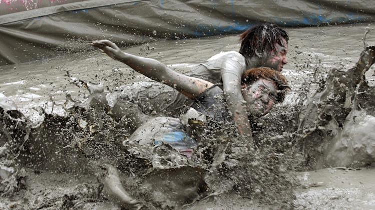 Men wrestle in a mud pool during the Boryeong Mud Festival at Daecheon Beach in Boryeong , South Korea, Friday, July 18, 2014. The 17th annual mud festival features mud wrestling and mud sliding.(AP Photo/Ahn Young-joon)