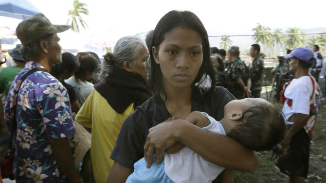 A mother cuddles her child as she lines up  for relief supplies at an evacuation center following Tuesday's typhoon, in New Bataan township, Compostela Valley in the southern Philippines, Thursday, Dec. 6, 2012.  The powerful typhoon that washed away emergency shelters, a military camp and possibly entire families in the southern Philippines has killed hundreds of people with nearly 400 missing, authorities said Thursday. (AP Photo/Bullit Marquez)