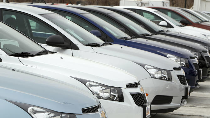 FILE - In this Feb. 19, 2012 file photo, a line of 2012 Chevrolet Cruze sedans sit at a dealership in the south Denver suburb of Englewood, Colo. The risk of engine fires is forcing General Motors to recall its Chevrolet Cruze compact cars, the company announced Friday, June 22, 2012. GM says the fires happen when fluids drip onto a plastic shield below the engine and ignite. GM knows of 30 fires caused by the problem. No injuries have been reported. The recall covers cars built from September 2010 through May 2012. (AP Photo/David Zalubowski, File)