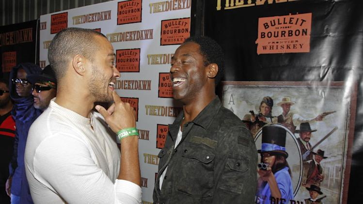 """IMAGE DISTRIBUTED FOR BULLEIT BOURBON - Jesse Williams, left, and Isaiah Washington share a laugh on the red carpet at the Bulleit Bourbon presents """"They Die By Dawn"""" premiere at SXSW on Saturday, March 16, 2013 in Austin, Texas. (Photo by Jack Plunkett/Invision for Bulleit Bourbon/AP Images)"""