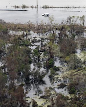 This aerial photo shows a car in floodwaters on Hwy. 23 in the aftermath of Hurricane Isaac. in Plaquemines Parish, La., Wednesday, Sept. 5, 2012. Thousands of electric customers are still without power, hundreds remained in shelters and several miles of coast line was tarred with weathered oil washing ashore, days after Isaac raked Louisiana. (AP Photo/Gerald Herbert)