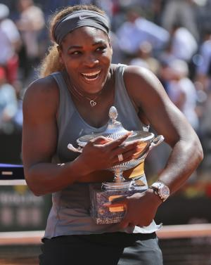 Serena Williams smiles as she holds the trophy after …