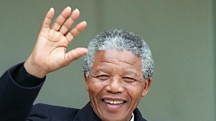 South African anti-apartheid leader and African National Congress (ANC) member Nelson Mandela waves to the press as he arrives at the Elysee Palace on June 7, 1990, in Paris