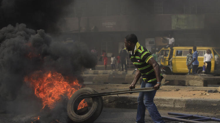"""FILE- An Unidentified man stocks the fire of a road block in the commercial capital of Lagos, Nigeria, during a fuel subsidy protest in this file photo dated Tuesday, Jan. 3, 2012, as angry mobs call on the government to keep a cherished consumer subsidy that had kept gas affordable for more than two decades. A 30-minute film documentary called """"Fuelling Poverty"""" has been online for months, but it is revealed Sunday April 21, 2013, that Nigerian officials have refused its director Ishaya Bako permission to show it publicly in this oil-rich nation, as it focuses on the January 2012 protests and the alleged billions of dollars thought to have been swallowed up by greedy companies and the nation's elite.(AP Photo/Sunday Alamba, FILE)"""