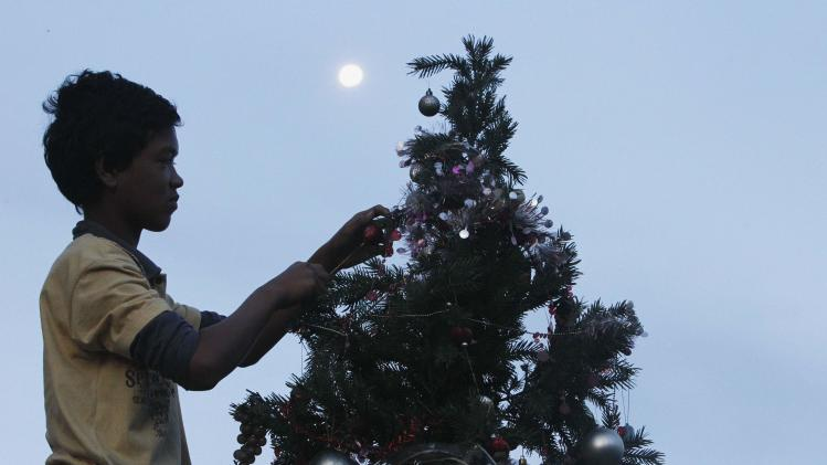 Ruben Miraflor, a survivor of Super Typhoon Haiyan, decorates Christmas tree placed along main street at Magallanes town in Tacloban