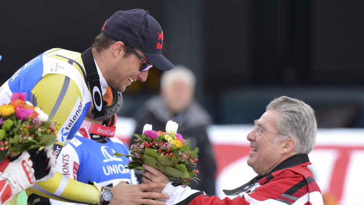 Norway's gold medal winner Aksel Lund Svindal receives flowers by Austrian President Heiny Fischer, right, after the men's downhill  at the Alpine skiing world championships in Schladming, Austria, Saturday, Feb. 9, 2013. (AP Photo/Kerstin Joensson)