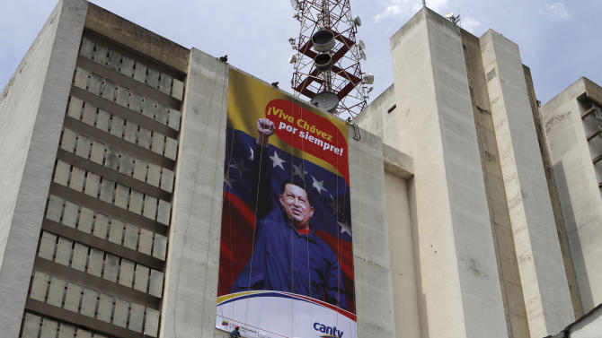 FILE - In this March 7, 2013 file photo, workers of the state-owned telephone company Cantv hang a banner honoring Venezuela's late President Hugo Chavez on the building housing the company's administrative offices, in Caracas, Venezuela. Politics rule everyday government in Venezuela, from state oil company to subways. State companies such as oil producer PDVSA and the manager of Caracas' subway system used to be known around the world for their professionalism. In recent years, many of those companies have seen service and revenue deteriorate as political cadres rather than engineers were brought in to run everything from oil exploration to mass transit. (AP Photo/Esteban Felix, File)