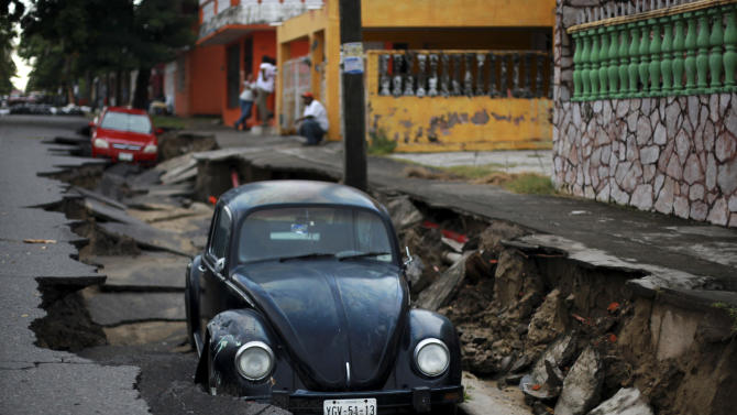 Cars sit on a street that collapsed after heavy rain in the Gulf port city of Veracruz, Mexico, Tuesday, Sept. 2, 2014. The Gulf states of Mexico are bracing for more bad weather as Tropical Storm Dolly crosses the coast and continues moving inland over northeastern Mexico on Wednesday. (AP Photo/Felix Marquez)