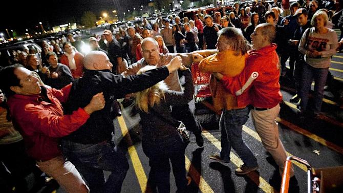 A crowd gathers as security guards break up a fight between shoppers waiting in line just as the doors open for Black Friday shopping at Target, Thursday, Nov. 22, 2012, in Bowling Green, Ky. Despite a surge of resistance as the sales drew near, with scolding editorials and protests by retail employees and reminders of frantic tramplings past, Black Friday's grip on America may be stronger than ever.  (AP Photo/Daily News, Alex Slitz)