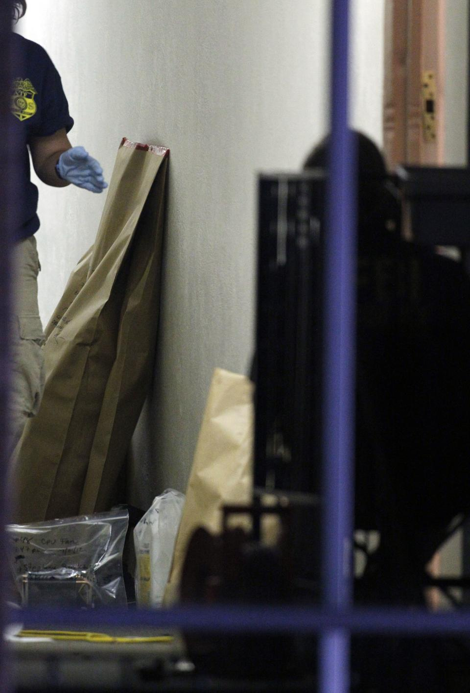 "Evidence removed from the apartment of alleged gunman James Holmes, lines the hallway outside his apartment, Saturday, July 21, 2012 in Aurora, Colo. Authorities reported that 12 died and more than three dozen people were shot during an assault at a movie theatre midnight premiere of ""The Dark Knight Rises."" (AP Photo/Alex Brandon)"