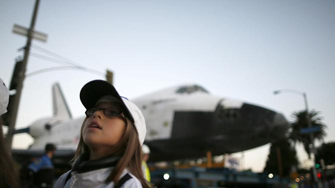 A girl poses in front of the space shuttle Endeavour as it is moved down the street, Saturday, Oct. 13, 2012 in Los Angeles. Endeavour's 12-mile road trip kicked off shortly before midnight Thursday as it moved from its Los Angeles International Airport hangar en route to the California Science Center, its ultimate destination. (AP Photo/Lucy Nicholson, Pool)